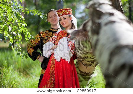 A man and a woman in the Russian festive national dress on the background of the forest