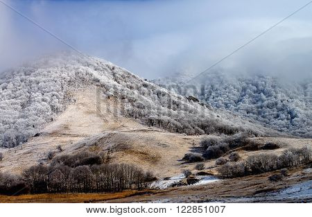 Snowy Mount Beshtau Ridges and Hills with Frozen Trees on Cloudy Sky background Outdoors