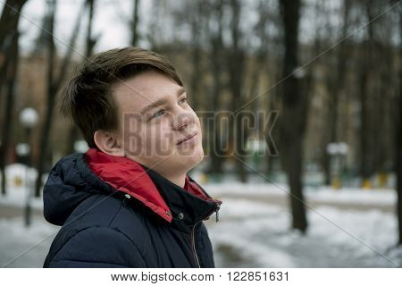 Early spring. Boy teenager in a warm jacket walks in the park.
