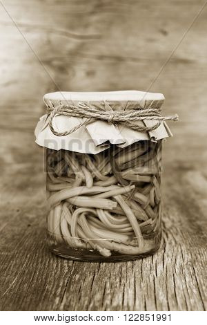 pickled garlic sprouts in glass jar closeup. home canning. black and white photo