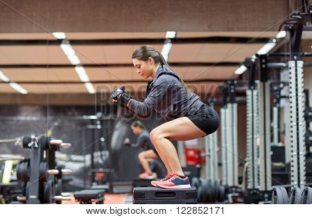 fitness, sport, exercising and people concept - woman doing squats on platform in gym
