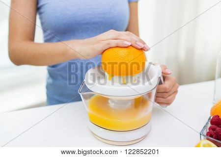 healthy eating, vegetarian food, dieting and people concept - close up of woman with squeezer squeezing orange juice at home