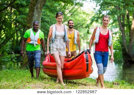 Friendy carying kajak to river in forrest