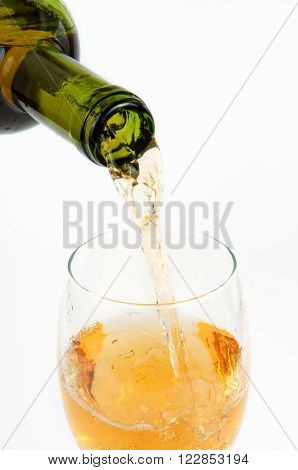 Pouring white wine from bottle into the wineglass closeup on white background