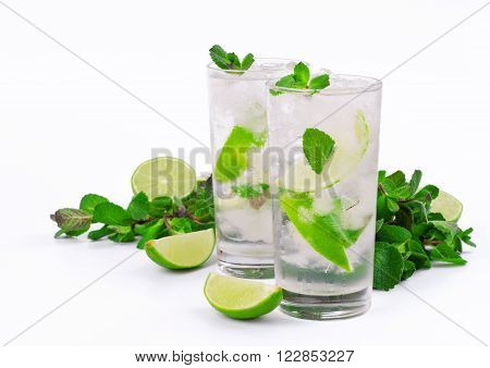 Two mojito cocktail with lime and mint in tumbler glass on white background
