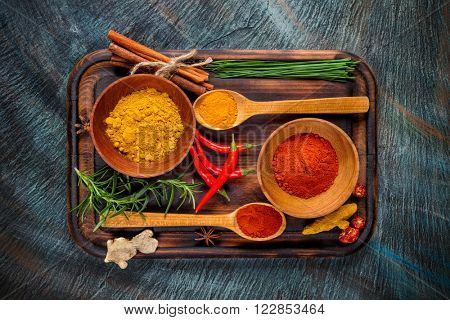 Overhead view of dried spices in bowls placed on breadboard