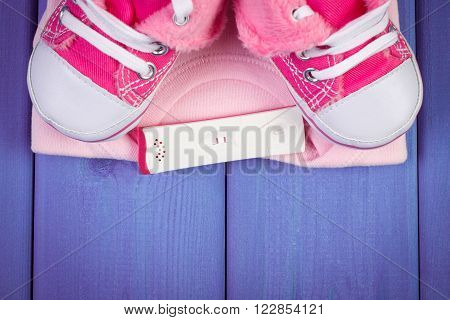 Pregnancy test with positive result and clothing for newborn on purple boards, concept of extending family and expecting for baby, copy space for text or inscription