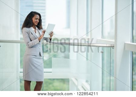 Malagasy business lady with tablet computer standing at big office window