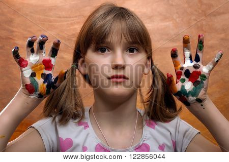 Emotional portrait of a girl. The palms in bright paint spots. The girl's beautiful eyes