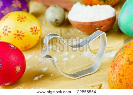 Easter food concept: preparation of holiday cookies shaped chick and colorful eggs on raw dough background. Shape for cookies as hen