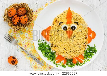 Traditional Easter salad shaped little fun chicken decorated egg yolk and vegetables. Creative food art idea on Easter meal party for children. Salad in style of animal-shape
