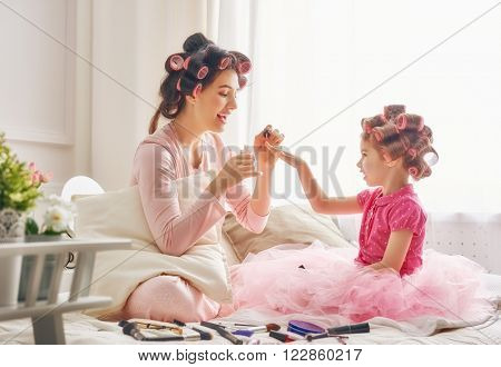 Happy loving family. Mother and daughter are doing hair, manicures and having fun. Mother and daughter sitting on the bed in the bedroom.