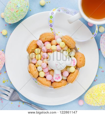 Easter bunny cute dessert for children. Easter treats candy cookies colorful eggs top view
