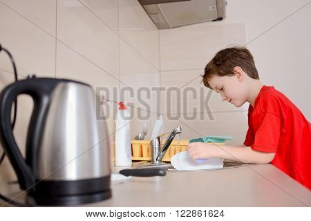 Happy, Smiling 7 Year Old Boy Washes Dishes
