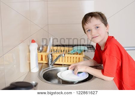 Smiling 7 Year Old Boy Washes Dishes