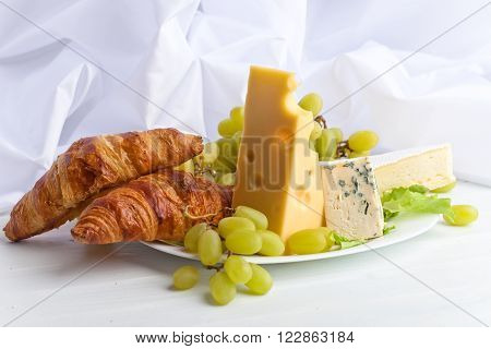 Various Cheeses With Grapes And Croissants
