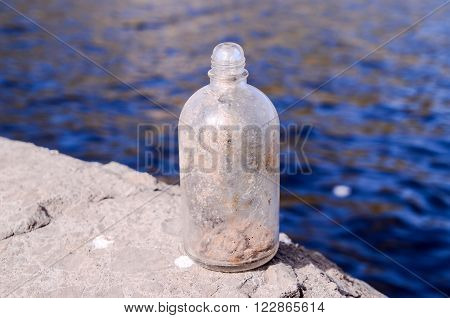 Old Dirty Vintage Gass Bottle near the Water