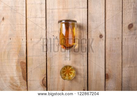 Bottle of brandy with a tumbler glass on a grunge wood surface