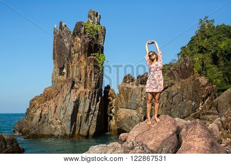 Young woman standing among the rocks on the coast.