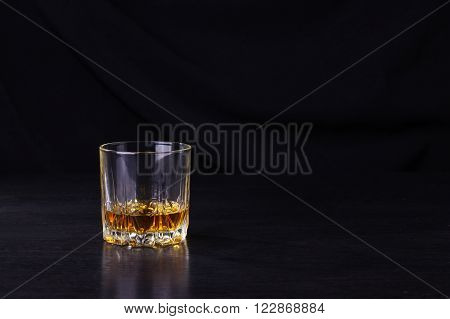 Tumbler glass with some whiskey on a black wooden surface
