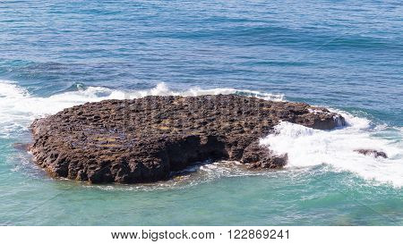 big brown stone - an island in the sea, birds sit on it and waves breaking on the rock and the water from the blue turns green