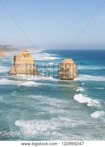 beautiful waves lapping on the beautiful rocky coast of large stones along the Great Ocean Road and unusual rock Twelve Apostles Victoria vertically Australia