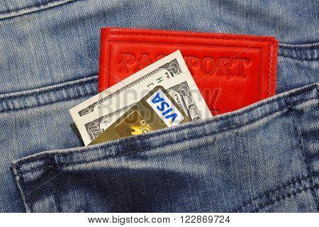 KHARKIV, UKRAINE - MARCH 16, 2016: American dollars, passport, credit cards Visa sticking out of the pocket of jeans