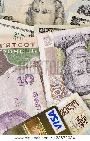 KHARKIV, UKRAINE - MARCH 16, 2016: American dollar,and money from different countries credit cards Visa