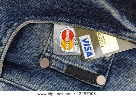 KHARKIV, UKRAINE - MARCH 16, 2016: Credit cards Visa and Mastercard sticking out of the pocket of jeans