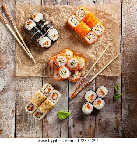 Set of Maki Sushi with Chopsticks on Parchment and Wooden Background