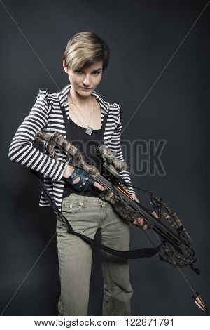 young woman with a big camouflage paint  crossbow