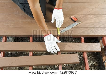 Worker installing wood floor for patio in construction site.