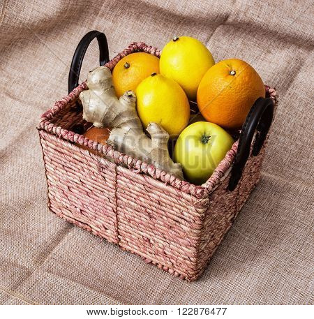 Wicker basket with apples oranges lemons and ginger on the cloth background. Healthy food.