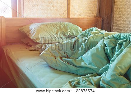 green pillow and blanket with wrinkle messy on bed in vintage wooden bedroom with lighting upper left side from sleeping in a long night winter.