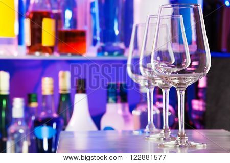 Wine glasses standing in a row on bar table with many bottles on background