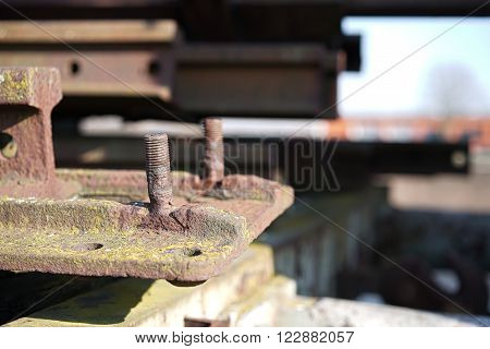 rusted component with screws at a junkyard