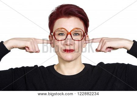 portarit of red-haired woman with big glasses holding her fingers to her ears