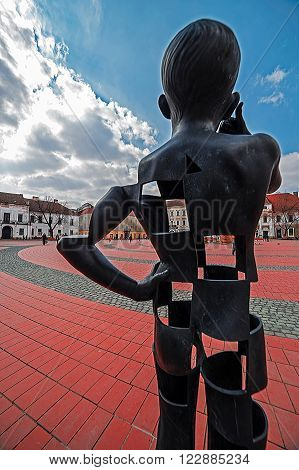 TIMISOARA ROMANIA - MARCH 18 2016: View of the Liberty-Square in Timisoara Romania with a modernist metal statue in the foreground.