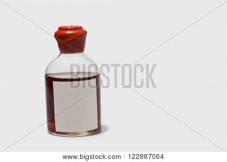 Vintage bottle with red wax cork brown booze and blank label. Retro style alcohol drink with sticker template. White background copy space