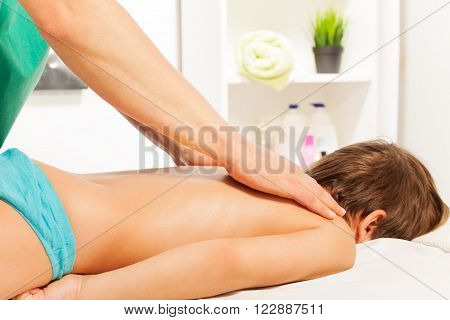Little boy lying on his stomach at the acupressure session in light massage room