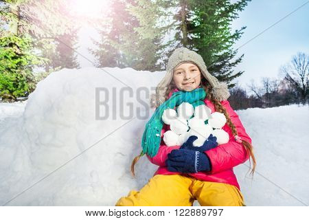 Happy girl have fun with snowball fight at winter forest