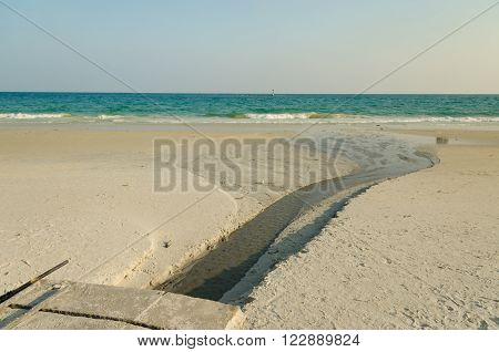Wastewater on golden sand beach with blue ocean.