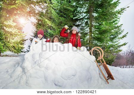 Children in winter forest playing snowballs, actively spending time outdoors