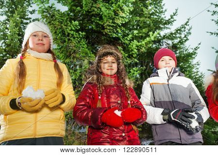 Boy and girls standing with snowballs in their hands preparing to play winter games