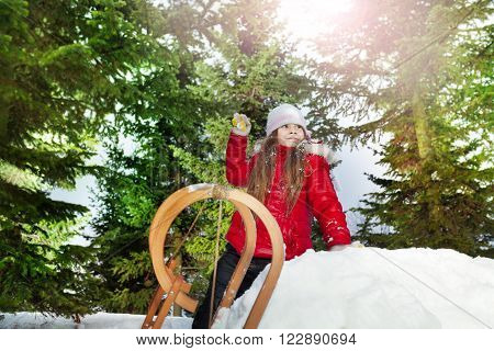 Beautiful girl plays in the snow with a snowball at the forest