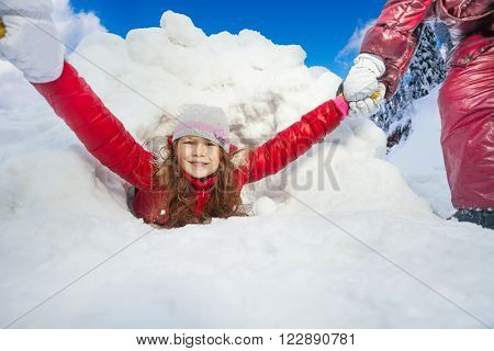 Friends are pulling smiling girl from the huge snow igloo