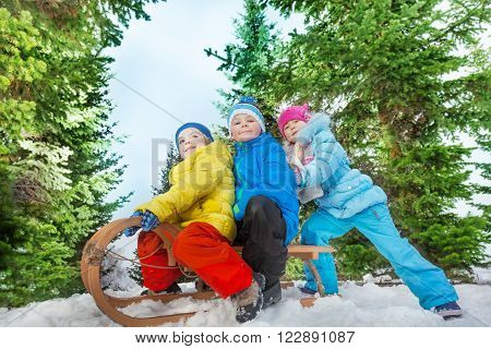 Group of kids in sledge go down on snow winter day in the trees
