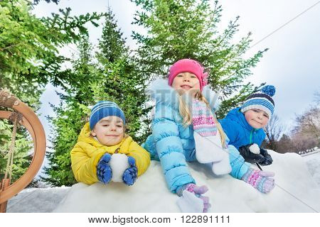 Kids boys and girls in colorful coats behind snow fortress wall throw snowballs