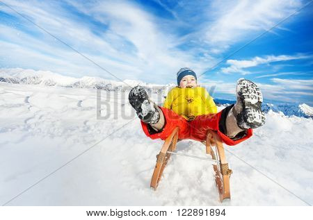 Little boy slide on sledge from the hill with legs first