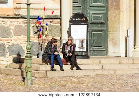 Kalmar Sweden - March 17 2016: Two women have a coffee break and a talk on the stone stairs outside a church. Easter decorations behind them. Real people in everyday life.